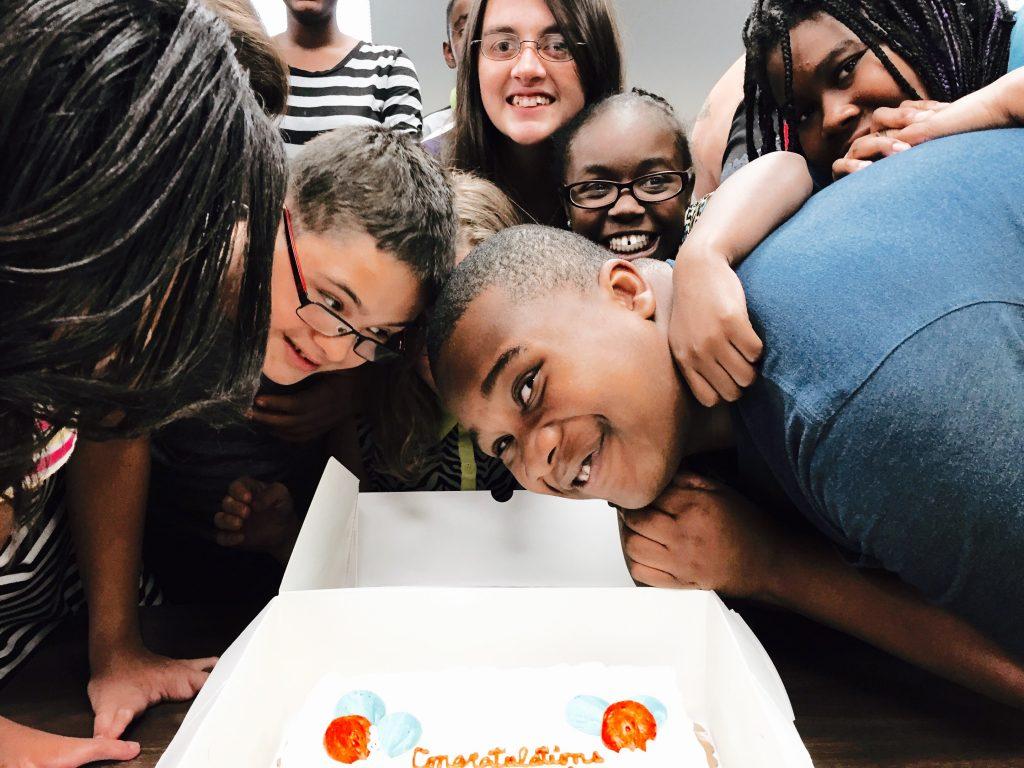 Image of youth surrounding cake