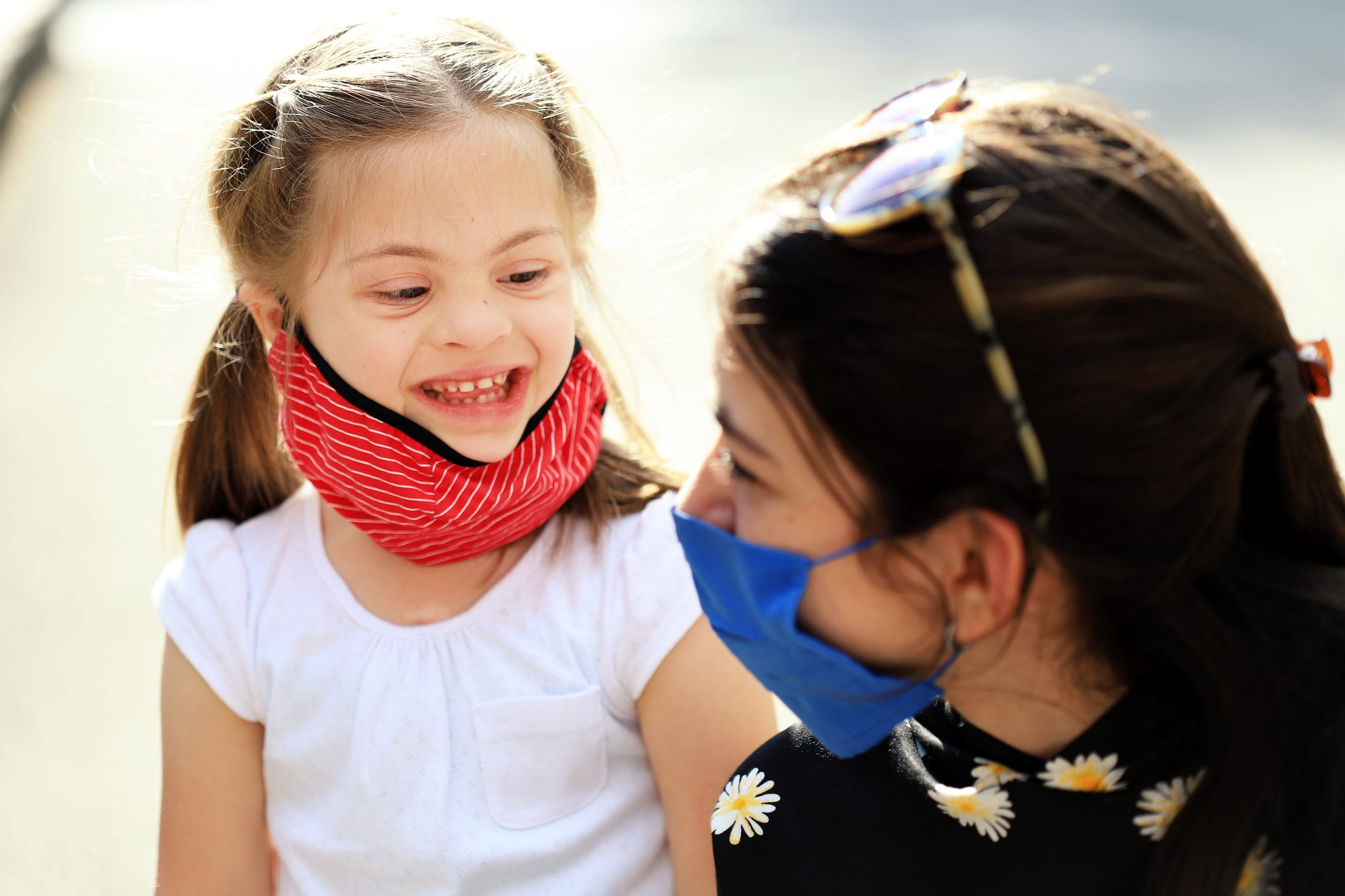 Two cheerful girls wearing face protective mask