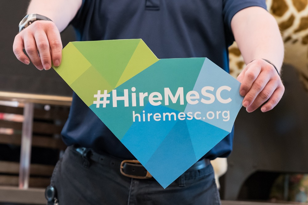 """A close-up of a person holding a """"Hire Me SC"""" flag in the shape of South Carolina."""