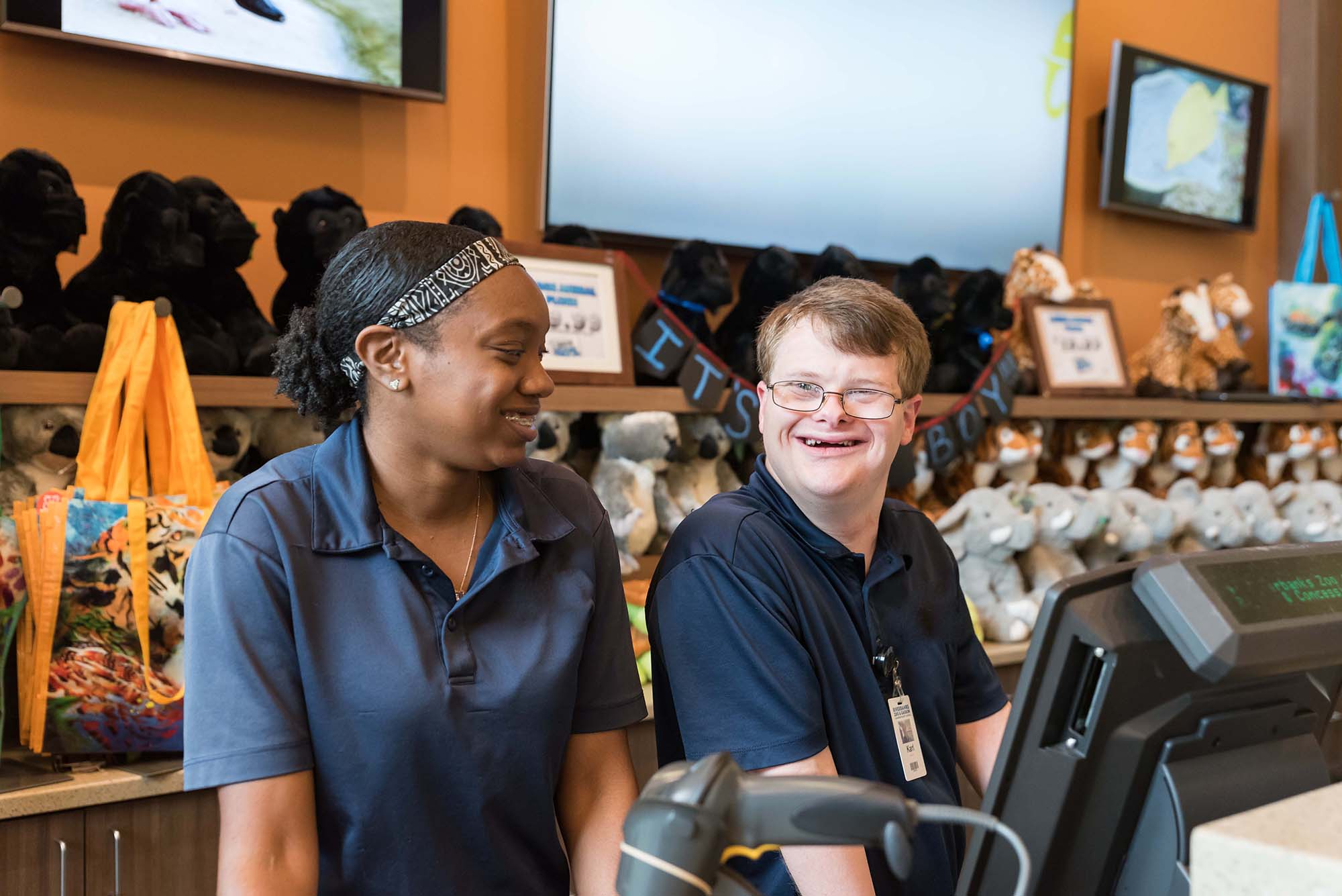 A Black woman and a white man with down syndrome wear blue collared shirts and stand behind the cash register, smiling.