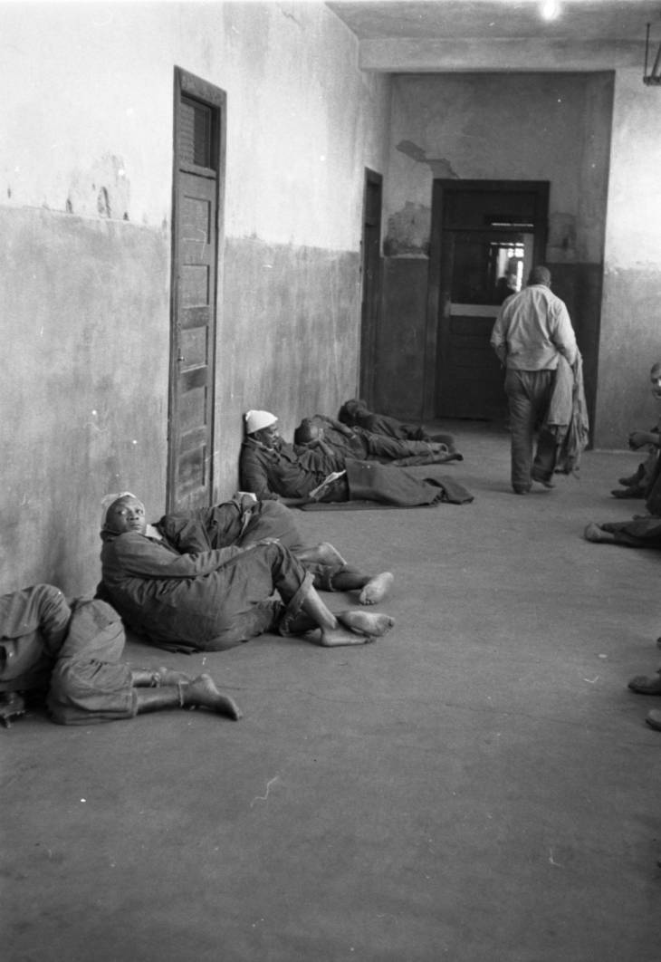 Black and white photograph of patients at the SC State Hospital in 1957. The walls and floor are concrete, and several patients are laying on the concrete floor.