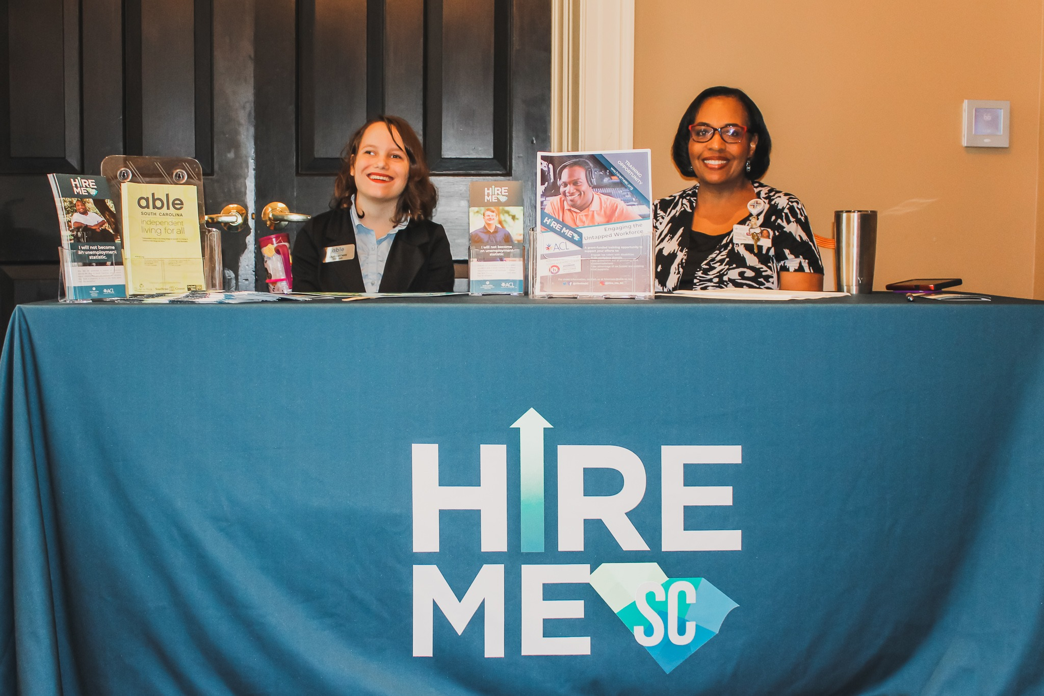 "Two women sit behind a vendor table with a large ""Hire Me SC"" tablecloth on it."