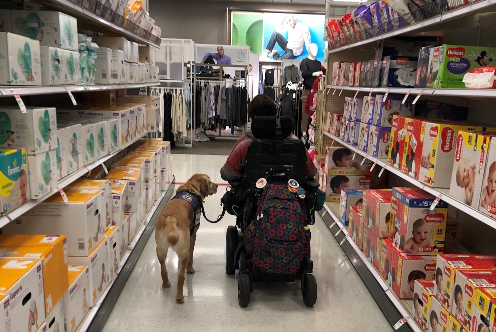 Dori is in her power wheelchair with her service dog Shack by her side, as they go down an aisle of the grocery store together.