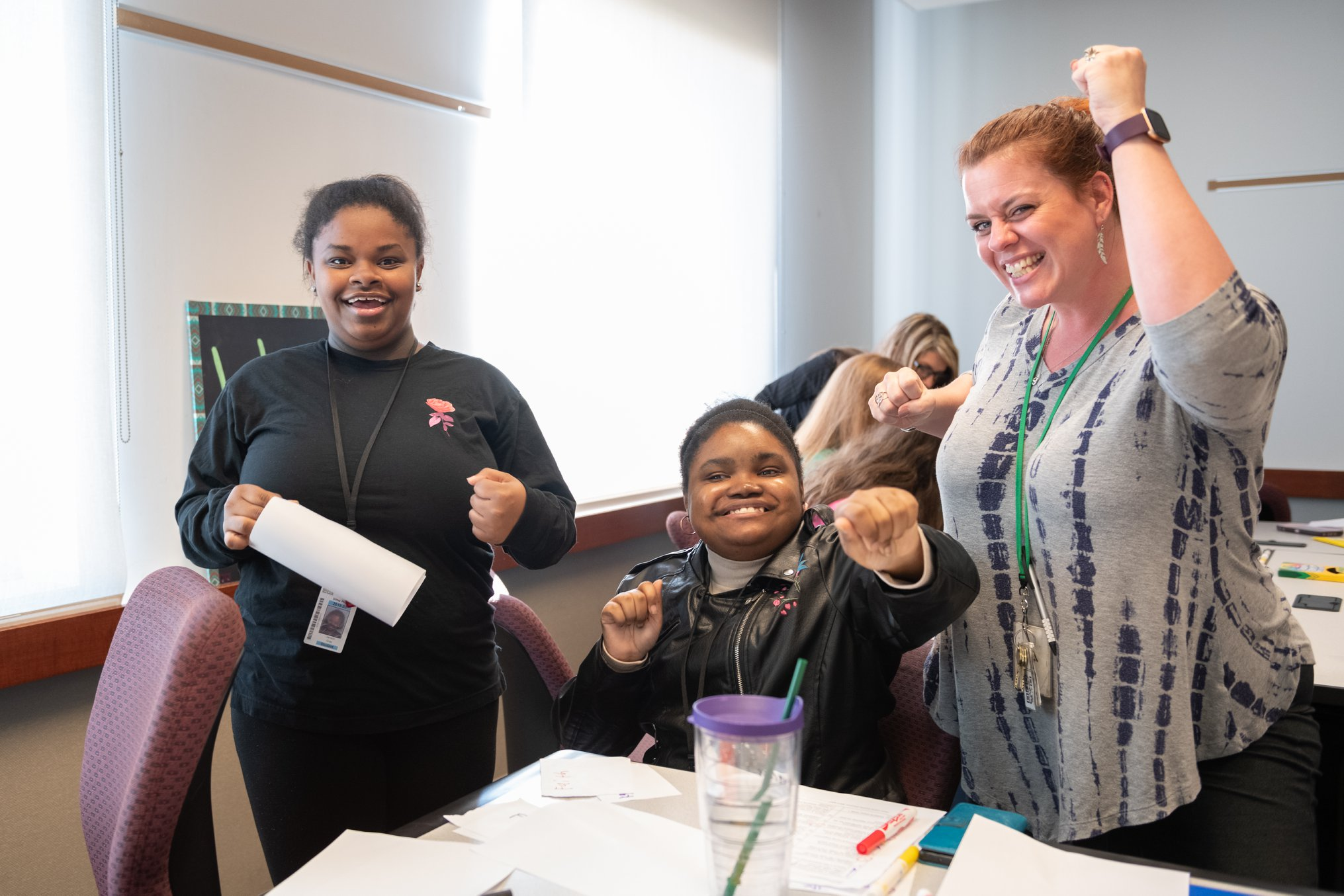 Two young Black women with disabilities smile and raise their fists in excitement while the teacher next to them does the same.