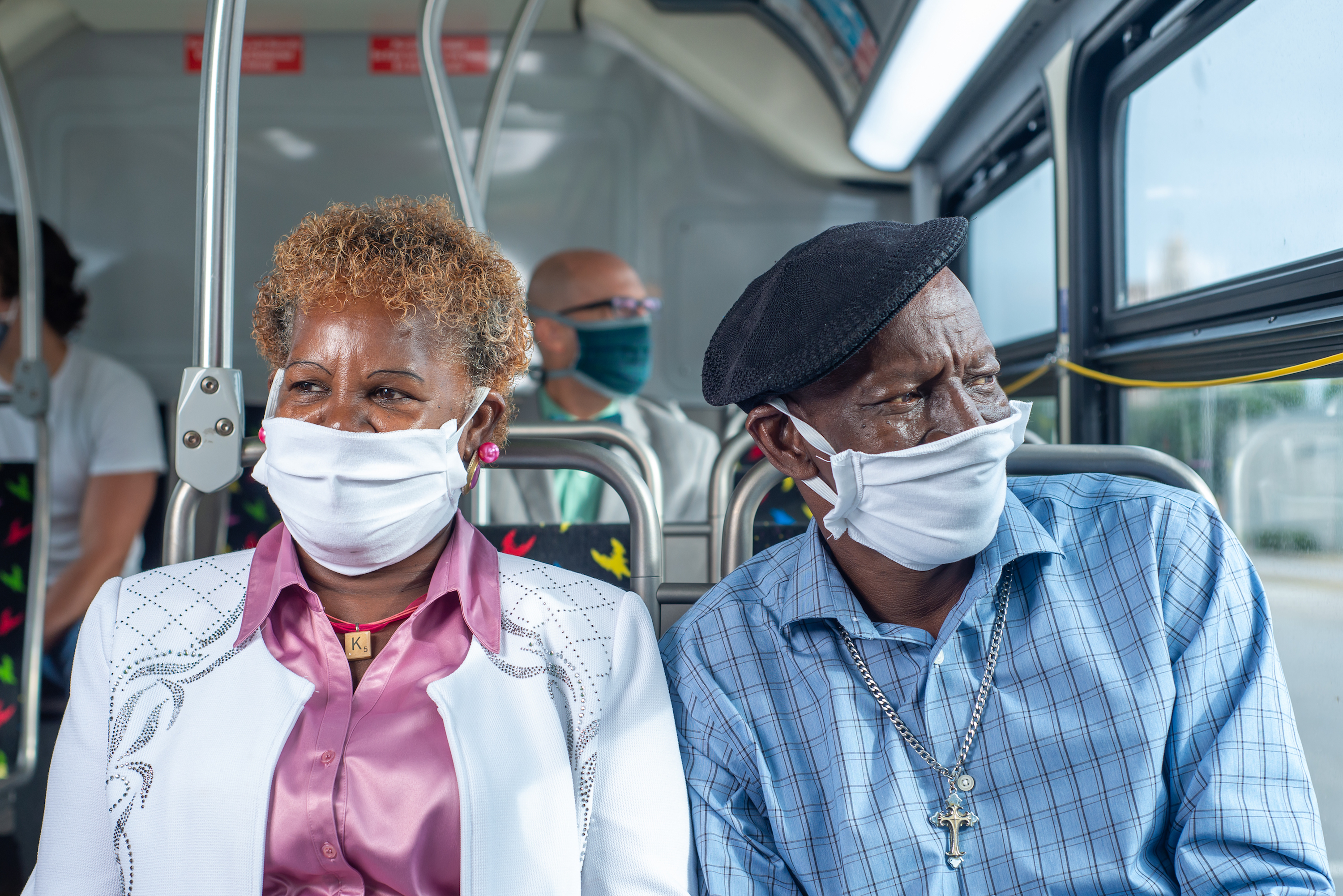 An older Black woman and man sit on a bus and wear masks.