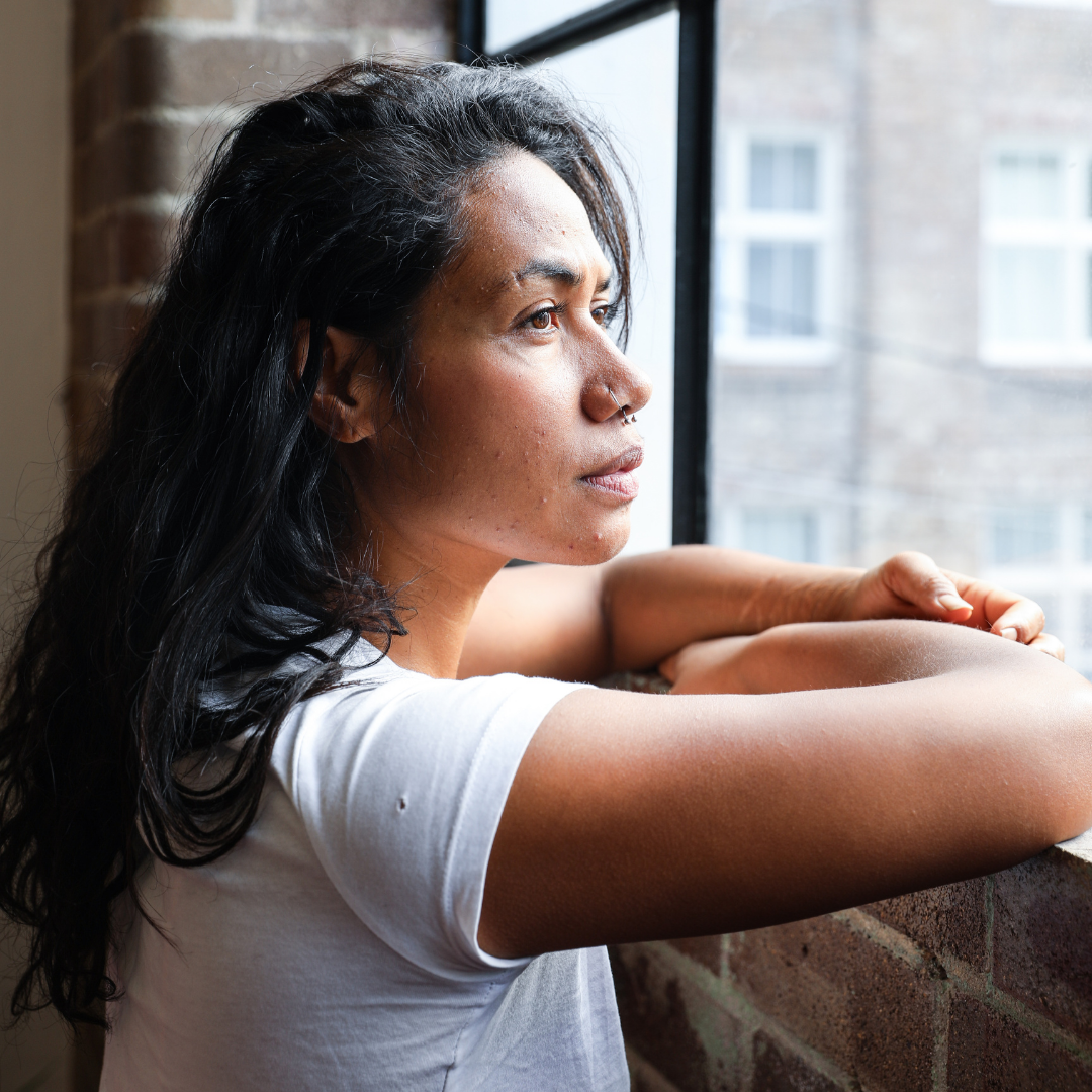 A woman with long, wavy black hair and a white t-shirt rests her arms on a brick windowsill and looks out the window longingly.