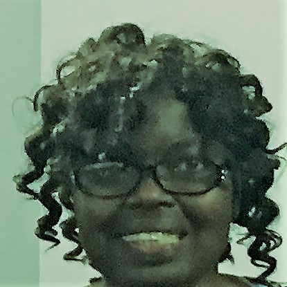 Angela, a Black woman, has curly black hair and glasses, and smiles.