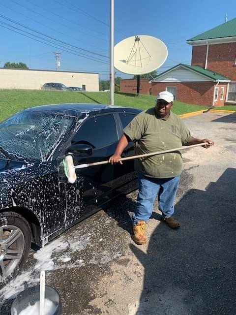 Abe is a Black man wearing a tshirt, jeans, and a baseball cap, and he is smiling while washing a car outside.