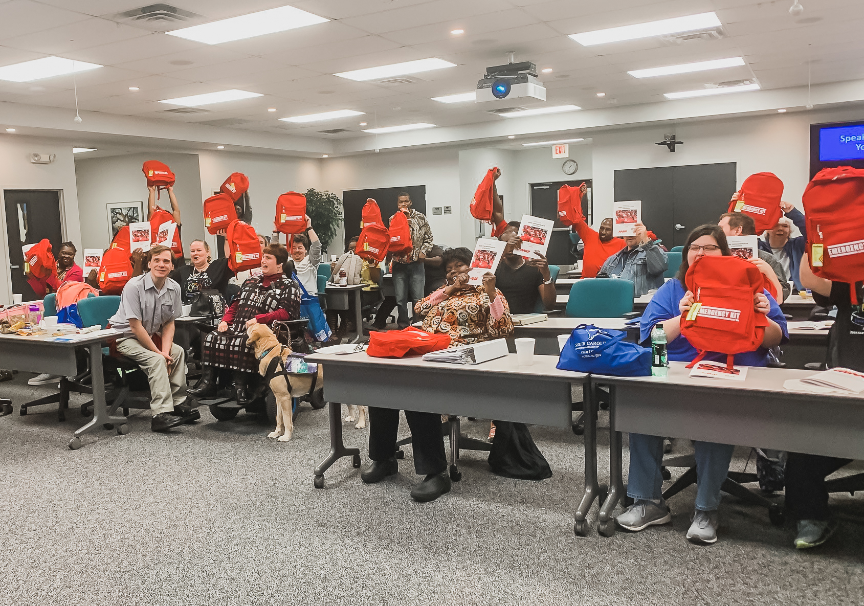 A group of individuals with disabilities sitting at tables, holding red emergency kit backpacks and smiling.